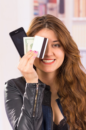 covering the face: modern beautiful young smiling woman holding cell phone, money and credit card covering face, concept of online shopping Stock Photo