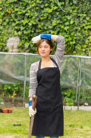 beautiful young woman gardening looking tired from working photo