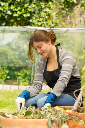 donna in ginocchio: bella giovane donna inginocchiata sul giardinaggio erba godendo all'aperto