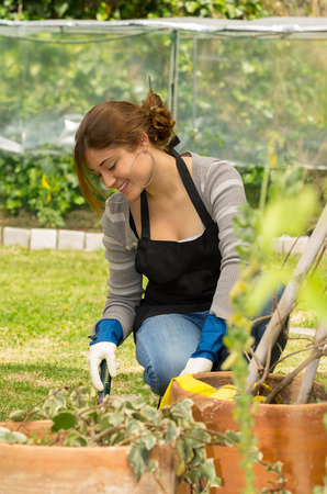 beautiful young woman gardening holding a spade outdoors photo