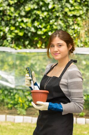 woman gardening: beautiful young woman gardening holding a pot