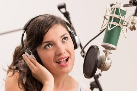 cantando: cantar chica morena joven y bella en el estudio de la m�sica Foto de archivo