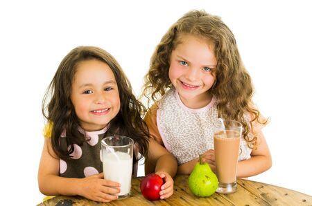 eating fruits: Lindas ni�as en edad preescolar beber leche y comer frutas aisladas en blanco Foto de archivo