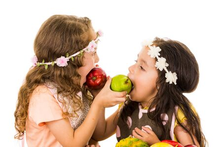 Beautiful healthy little girls feeding each other delicious fresh fruits isolated on white photo