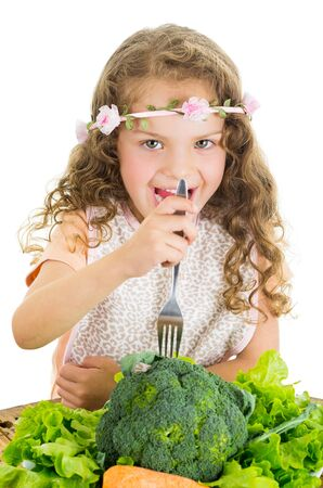 Beautiful healthy little curly girl enjoying eating broccoli isolated on white photo