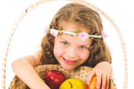 Cute little happy preschooler girl with fruits on the table isolated on white photo