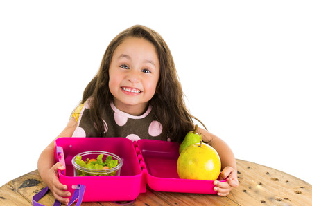food box: Cute little brunette girl with her healthy lunchbox isolated on white