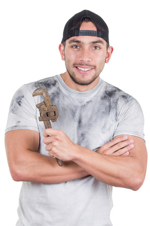 happy young muscular latin construction worker holding a wrench isolated on white photo
