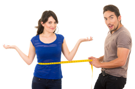 slim tummy: handsome astonished man holding measuring tape around thin fit young girls waist concept of dieting fitness weightloss  isolated on white