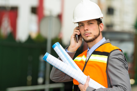 young handsome architect supervising a construction using cell phone with buildings in the background photo