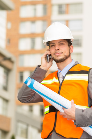 young handsome architect supervising a construction talking on cell phone outdoors photo
