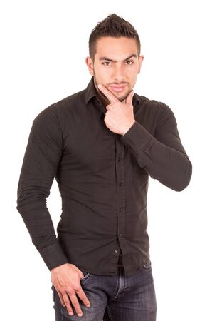 hand on the chin: handsome brunette young man wearing black shirt with hand on chin isolated on white