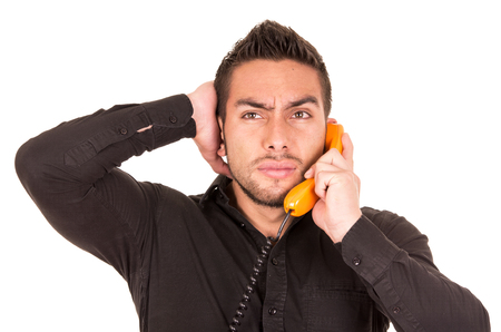 corded: closeup portrait of handsome worried hispanic man talking on corded retro phone isolated on white Stock Photo