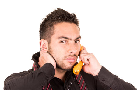 closeup portrait of handsome hispanic man talking on corded retro phone with hand on neck isolated on white photo
