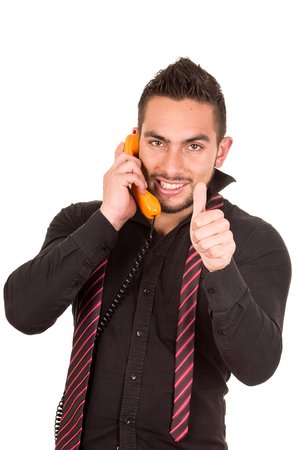 corded: closeup portrait of handsome hispanic man talking on corded retro phone with thumb up isolated on white