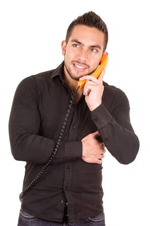 corded: closeup portrait of handsome happy hispanic man talking on corded retro phone isolated on white Stock Photo