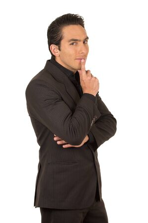 handsome elegant young latin man wearing a suit posing gesturing silence isolated on white Stock Photo