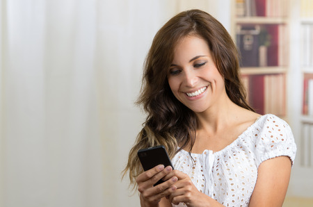 young casual beautiful hispanic woman texting with her cell phone