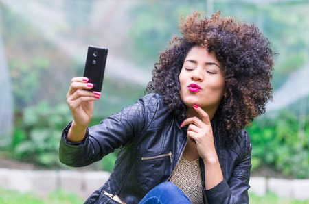exotic beautiful young girl with dark curly hair taking selfie with her cell phone sitting in the garden photo