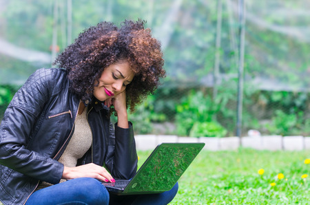 saddened: exotic beautiful young worried girl with dark curly hair using laptop in the garden