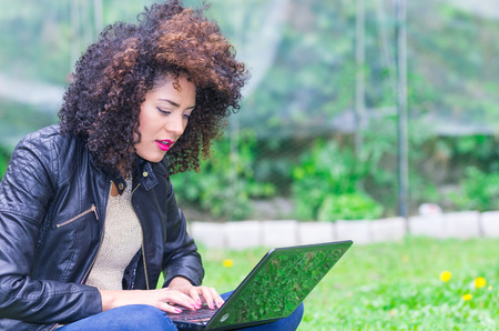 exotic beautiful young girl with dark curly hair using laptop typing in the garden