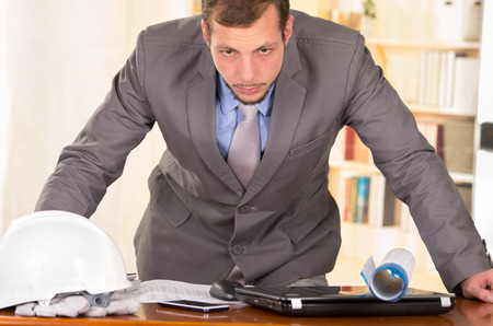 young handsome busy architect leaning on his desk working looking stressed photo