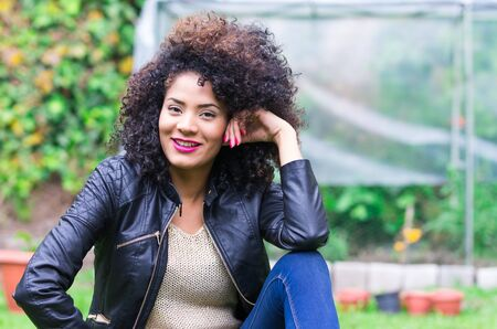 exotic beautiful young girl with dark curly hair relaxing in the garden photo