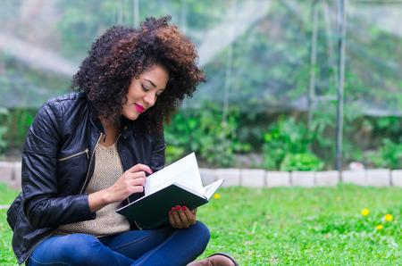 巻き毛を持つ暗いリラックスできる本を読んで庭にエキゾチックな美しい少女