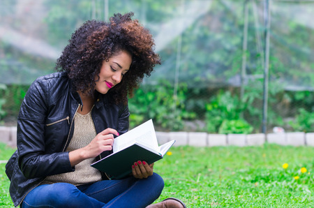 exotic beautiful young girl with dark curly hair relaxing in the garden reading a book photo