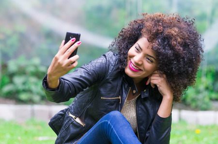 people: exotic beautiful young girl with dark curly hair taking selfie with her cell phone sitting in the garden