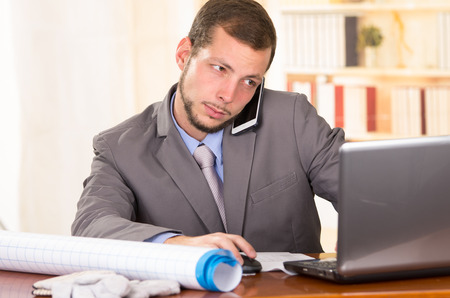 young handsome architect working in office using cell phone and laptop photo