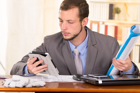 young handsome busy architect sitting in front of his desk working using tablet photo