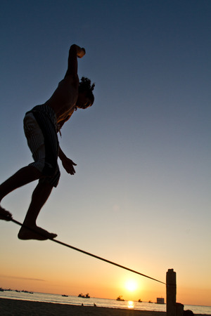 slack: Silhouette of young man balancing on slackline during sunset at a beach in Manabi, Ecuador. Low angle