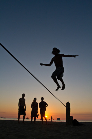 slack: Silhouette of young man balancing jumping on slackline during sunset at a beach in Manabi, Ecuador