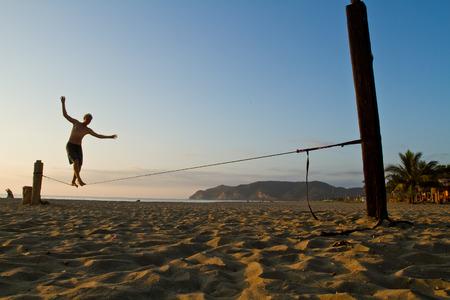 MANABI, ÉQUATEUR - 5 juin 2012: Unidentified jeune homme en équilibre sur slackline à une plage de Manabi.