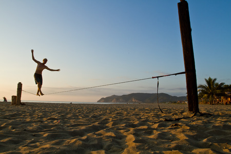 MANABI, ECUADOR - JUNE 5, 2012: Unidentified young man balancing on slackline at a beach in Manabi. Zdjęcie Seryjne - 39325377
