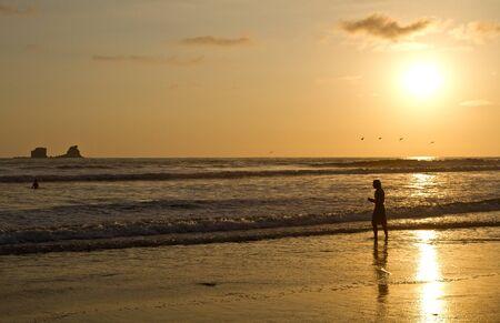 ruta: Silhouette of young man enjoying the beach view during sunset in Manabi, Ecuador