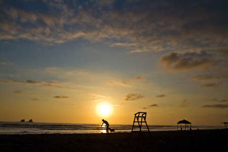 ruta: Beautiful sunset view from Ayampe beach in Manabi, Ecuador. Silhouette of a man with dog