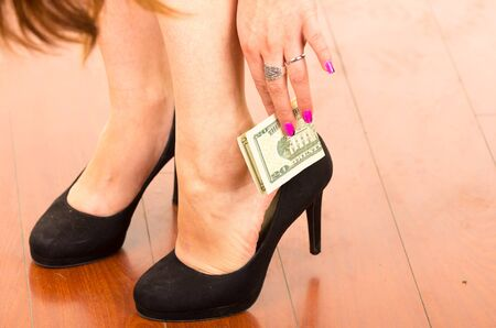 superstitious: Close up of superstitious womans hand putting a dollar bill inside shoe