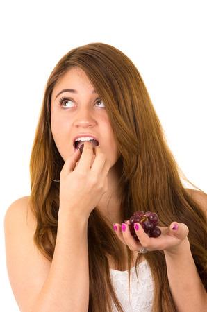 kabbalah: Close up shot of beautiful young supersticious woman eating grapes