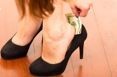 putting up: Close up of superstitious womans hand putting a dollar bill inside shoe