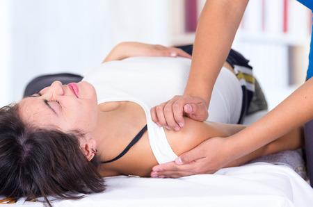 fisioterapia: mujer joven en el dolor que miente mientras que consigue un masaje desde el concepto especializado de fisioterapia