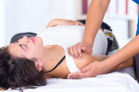 young woman in pain lying while getting a massage from specialist concept of physiotherapy