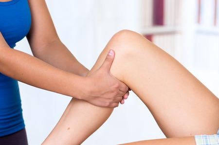 human knee: young woman lying while getting a leg massage from specialist concept of physiotherapy. Close up