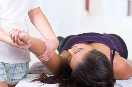 masaje deportivo: joven mujer tumbada al obtener un masaje de brazo desde el concepto especializado de fisioterapia