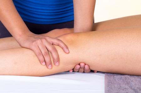 massaggio: giovane donna distesa mentre ottiene un massaggio alle gambe dal concept specialista di fisioterapia. Avvicinamento Archivio Fotografico