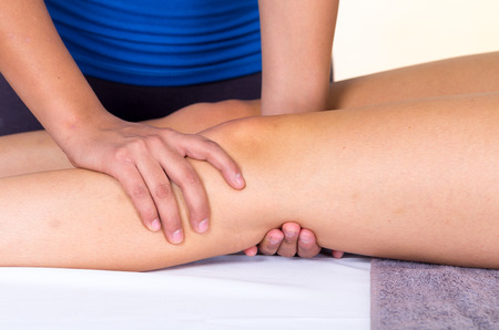 knees: young woman lying while getting a leg massage from specialist concept of physiotherapy. Close up
