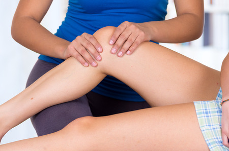sports massage: joven mujer tumbada mientras que consigue un masaje de piernas desde el concepto especializado de fisioterapia. Acercamiento