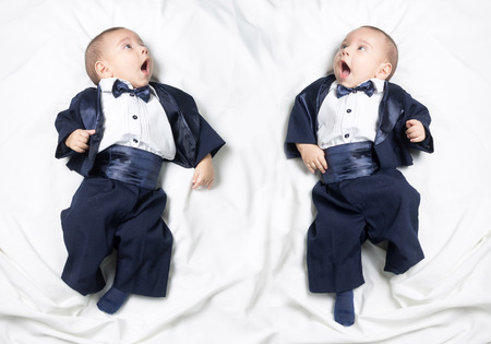 Mirrored photo of cute infant baby boy wearing elegant tuxedo with bow tie photo