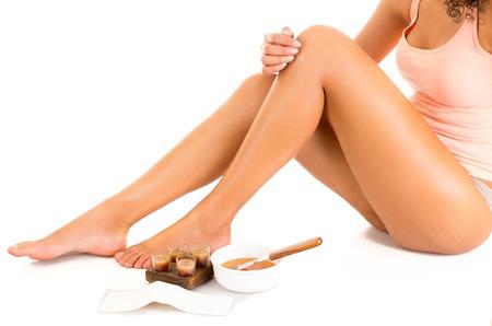 depilacion con cera: Mujer hermosa joven latino con la piel sedosa acariciando sus piernas, el concepto de depilación piernas, aislado en blanco